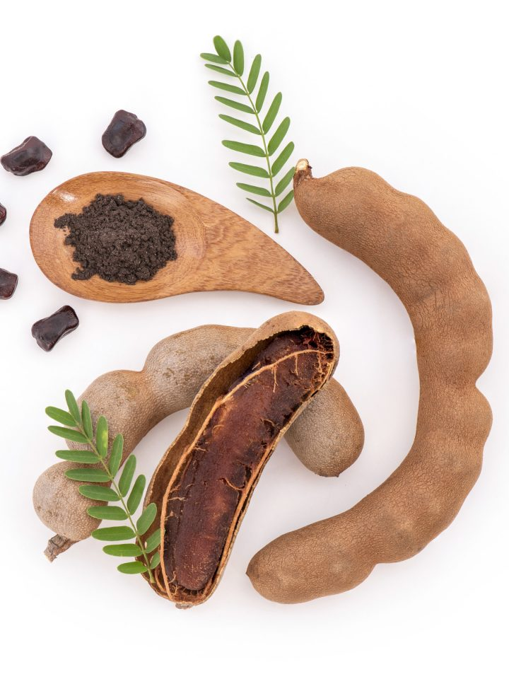 Tamarind fruits with seeds on white surface