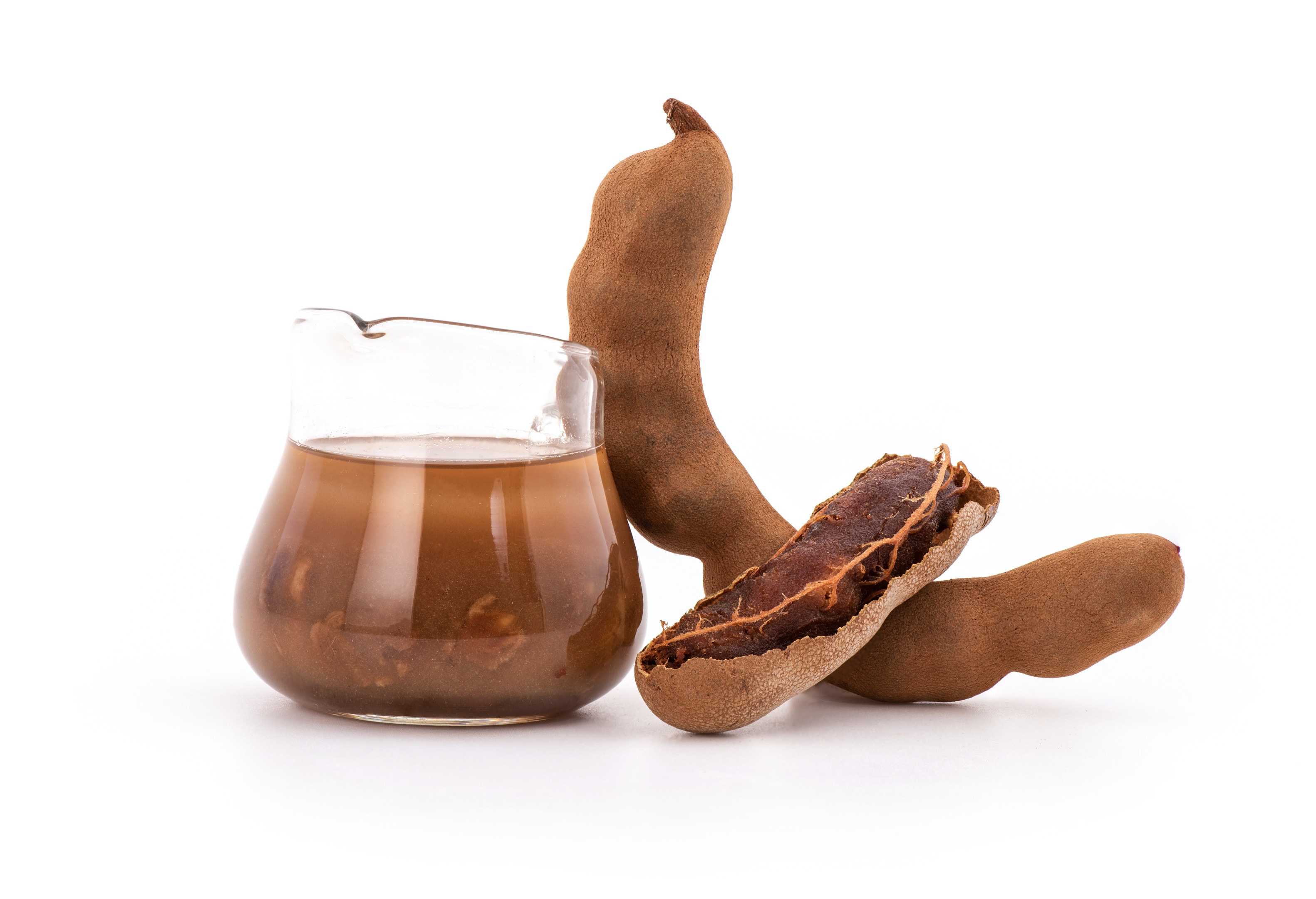 Tamarind fruits with tamarind pulp mixed with water in a glass