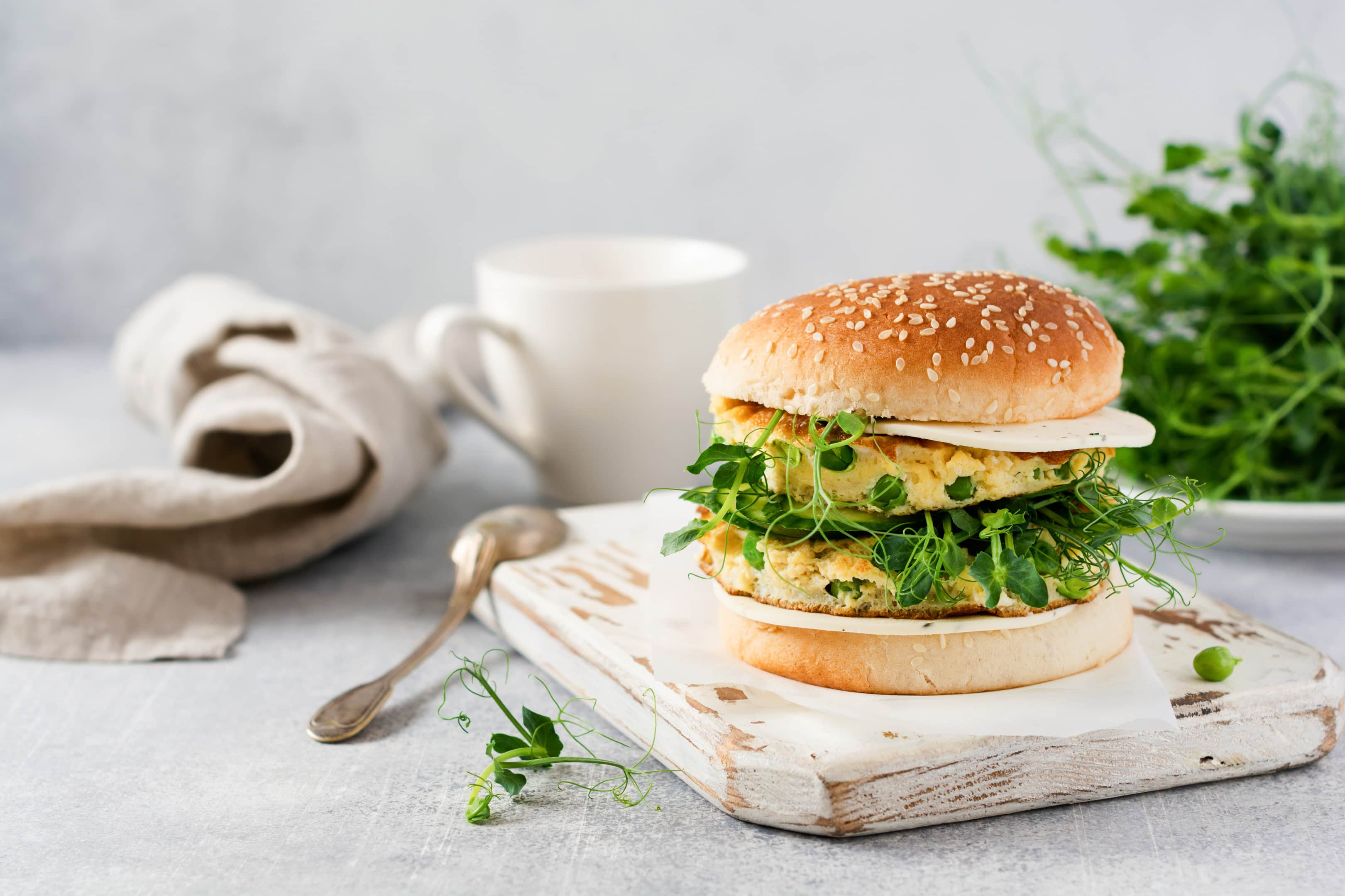 Vegetarian burger with egg and pea shoots on wooden cutting board