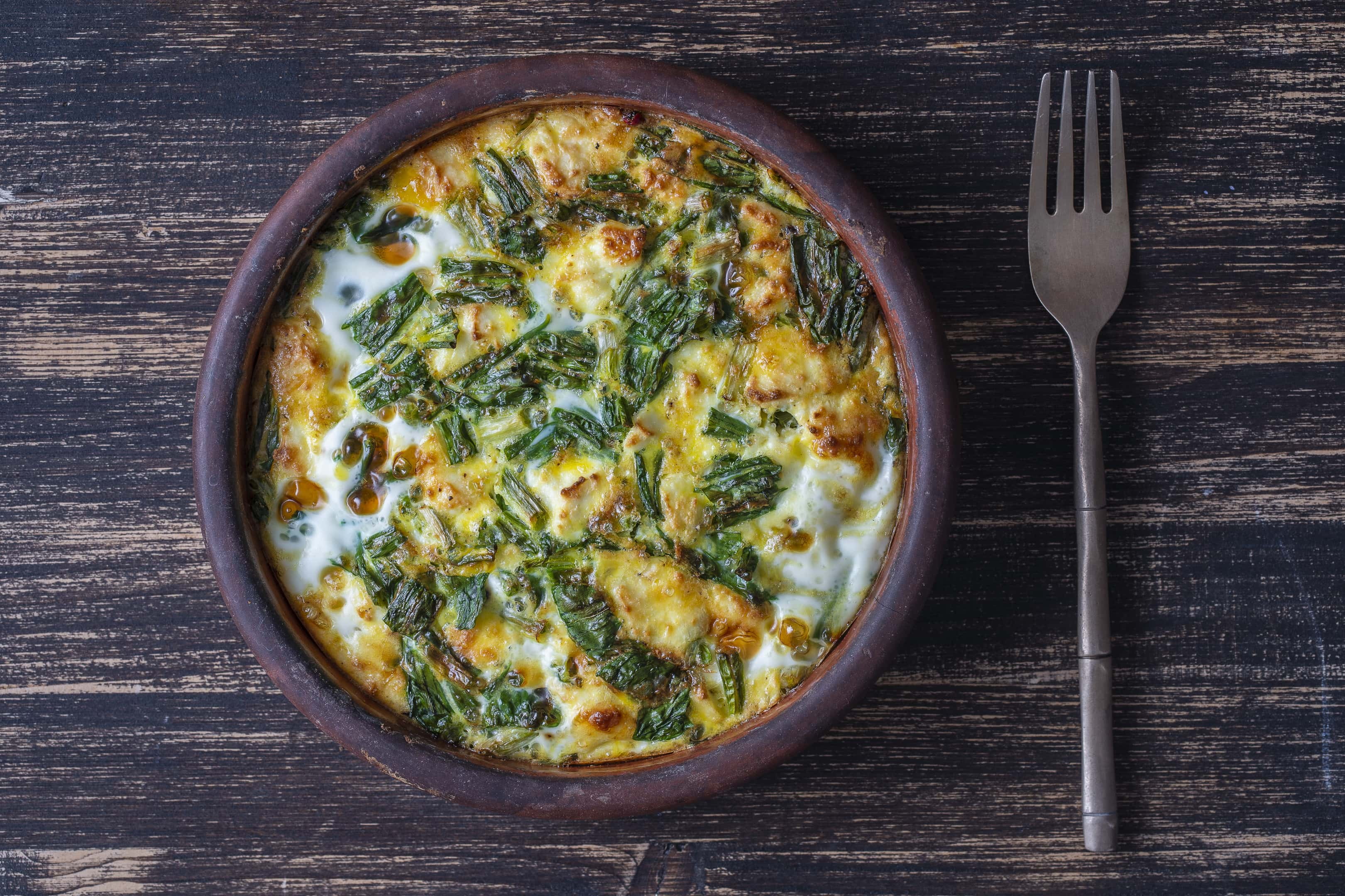 Vegetarian frittata with ramps wild leeks leaves, pepper, onion, cheese and green wild garlic leaves