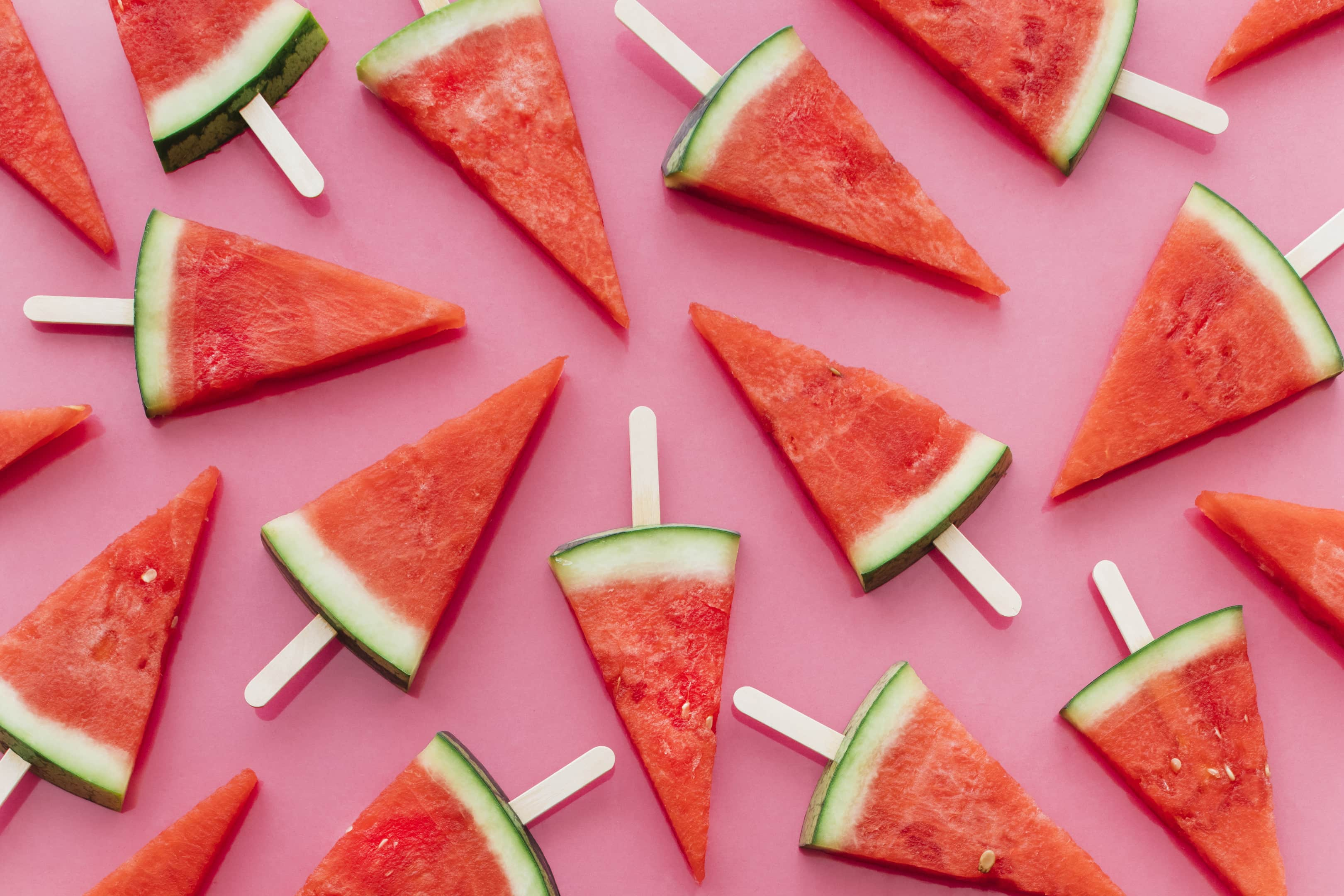 Watermelons on sticks on pink background