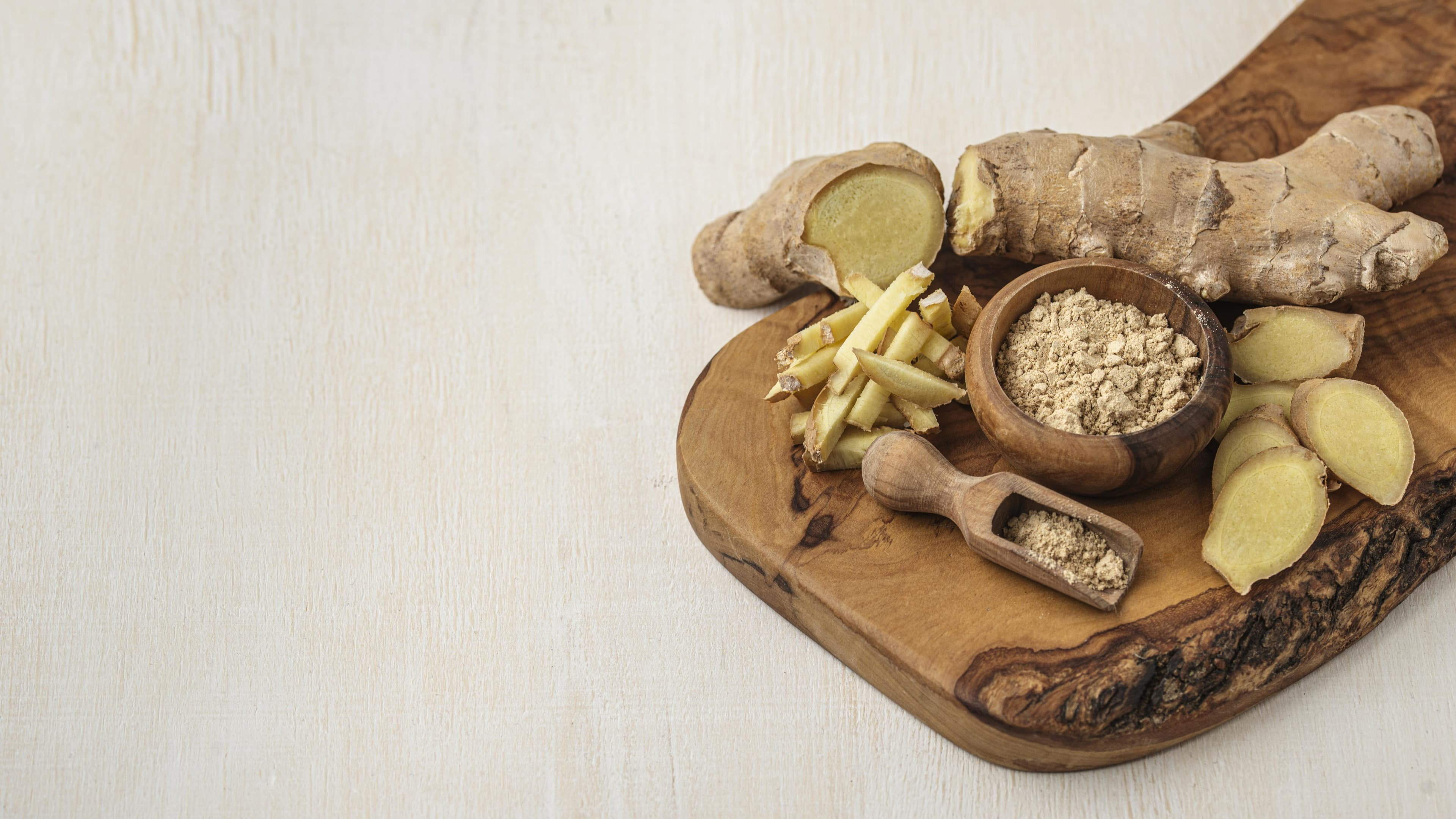 Assortment of fresh and powdered ginger on wooden board