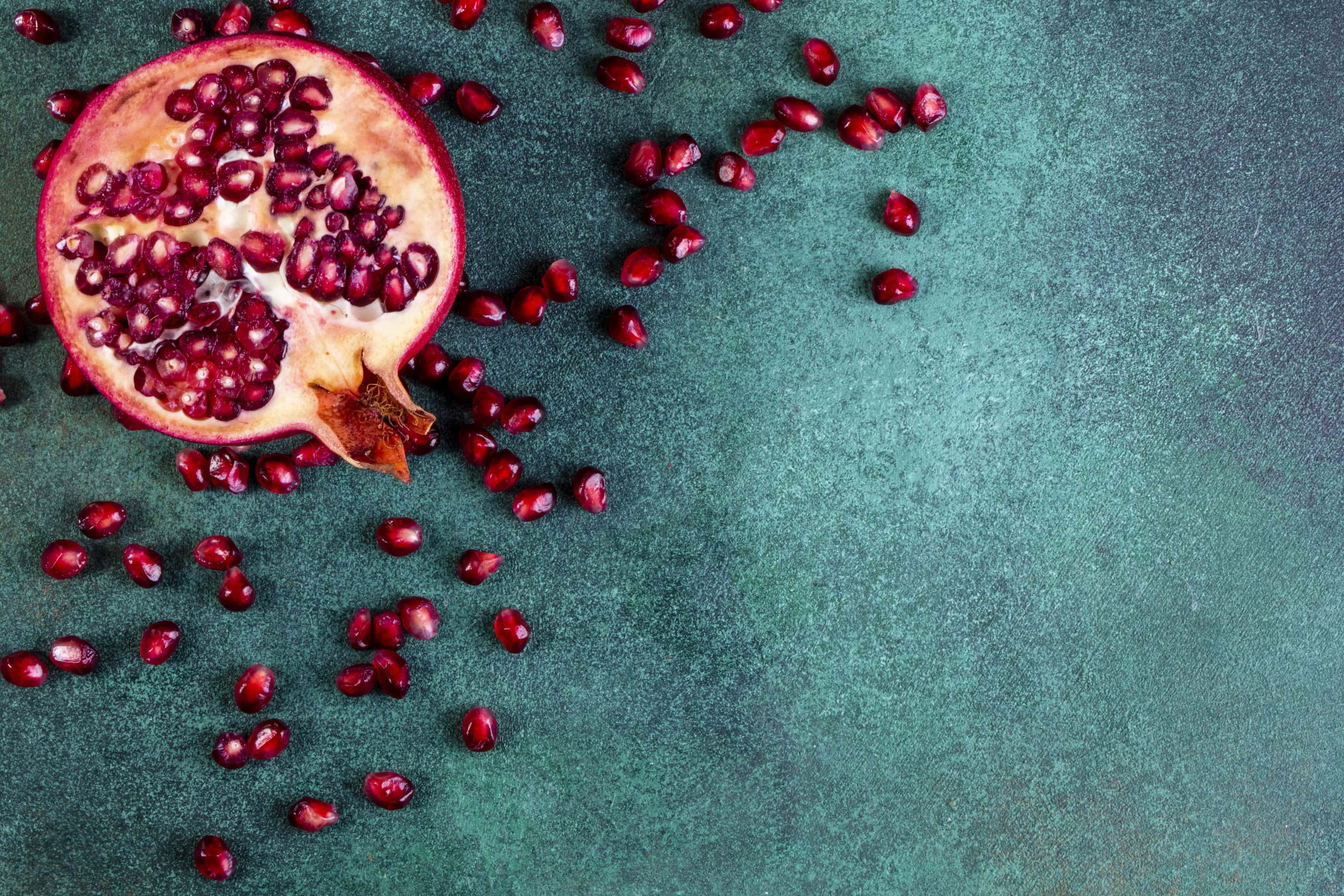 Chopped half of pomegranate on green table
