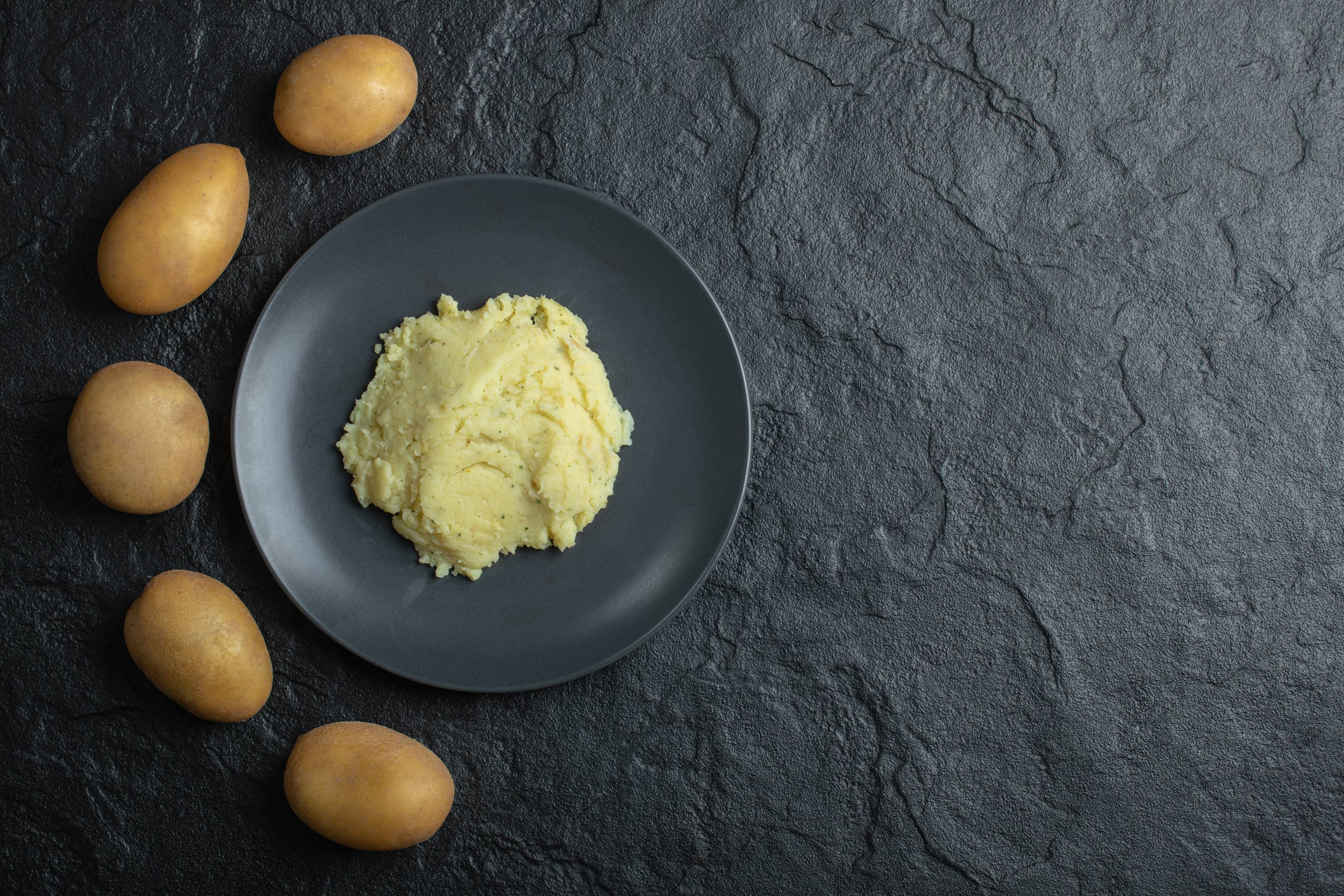 Fresh potatoes and mashed potatoes on black table