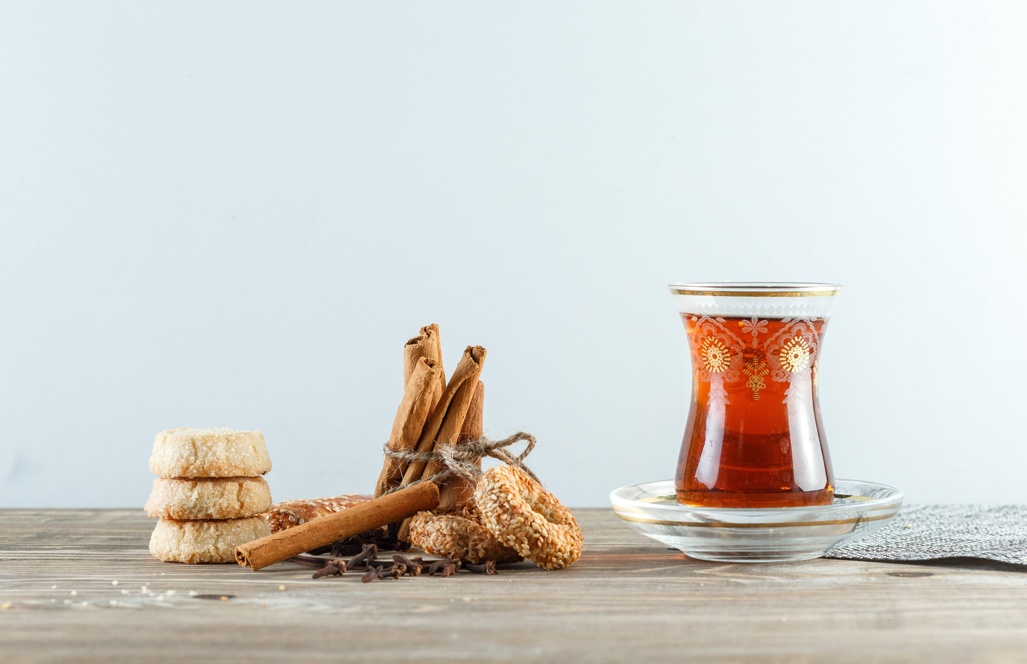 Glass of tea with cloves and biscuits