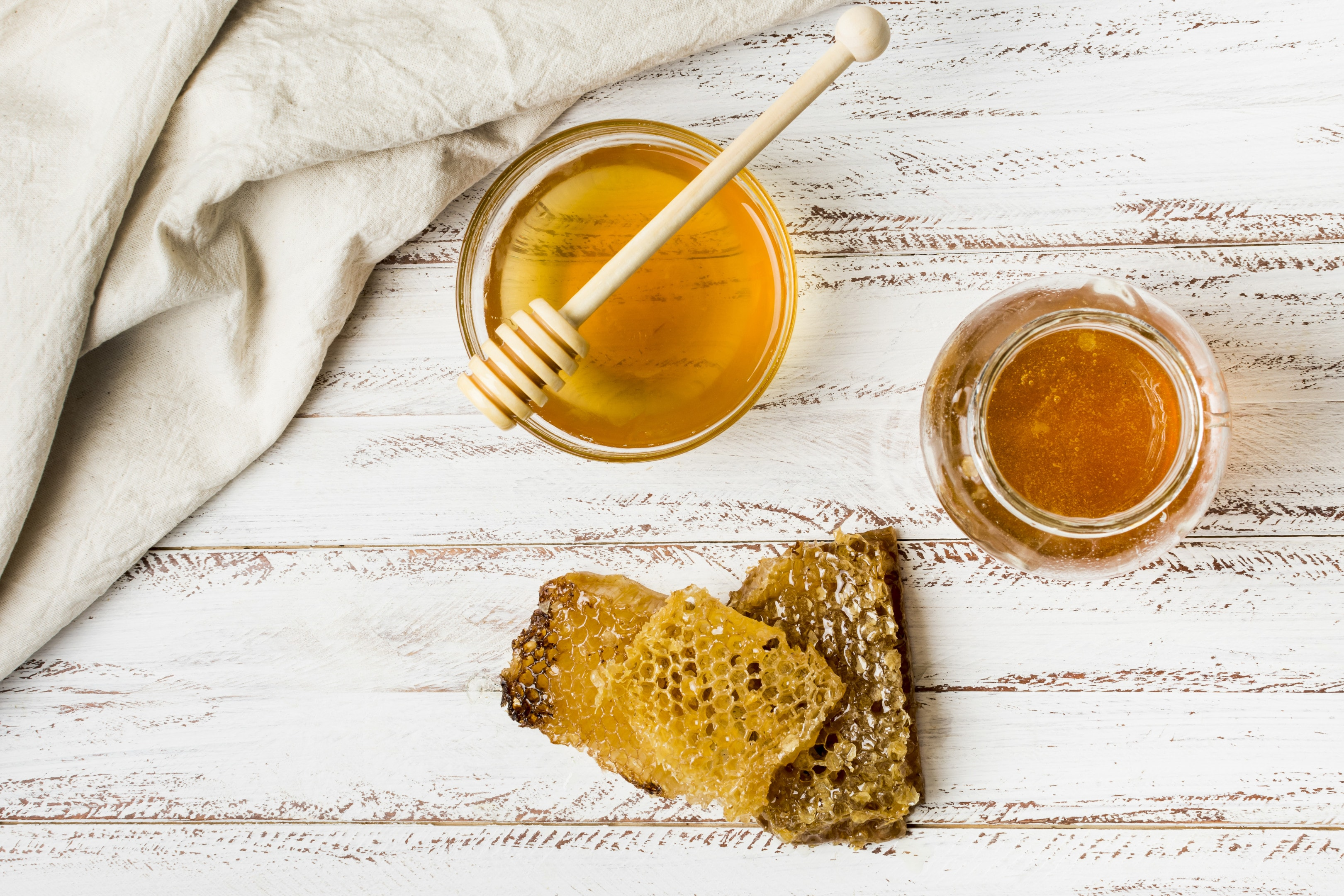 Honey jars with honeycomb on wooden table