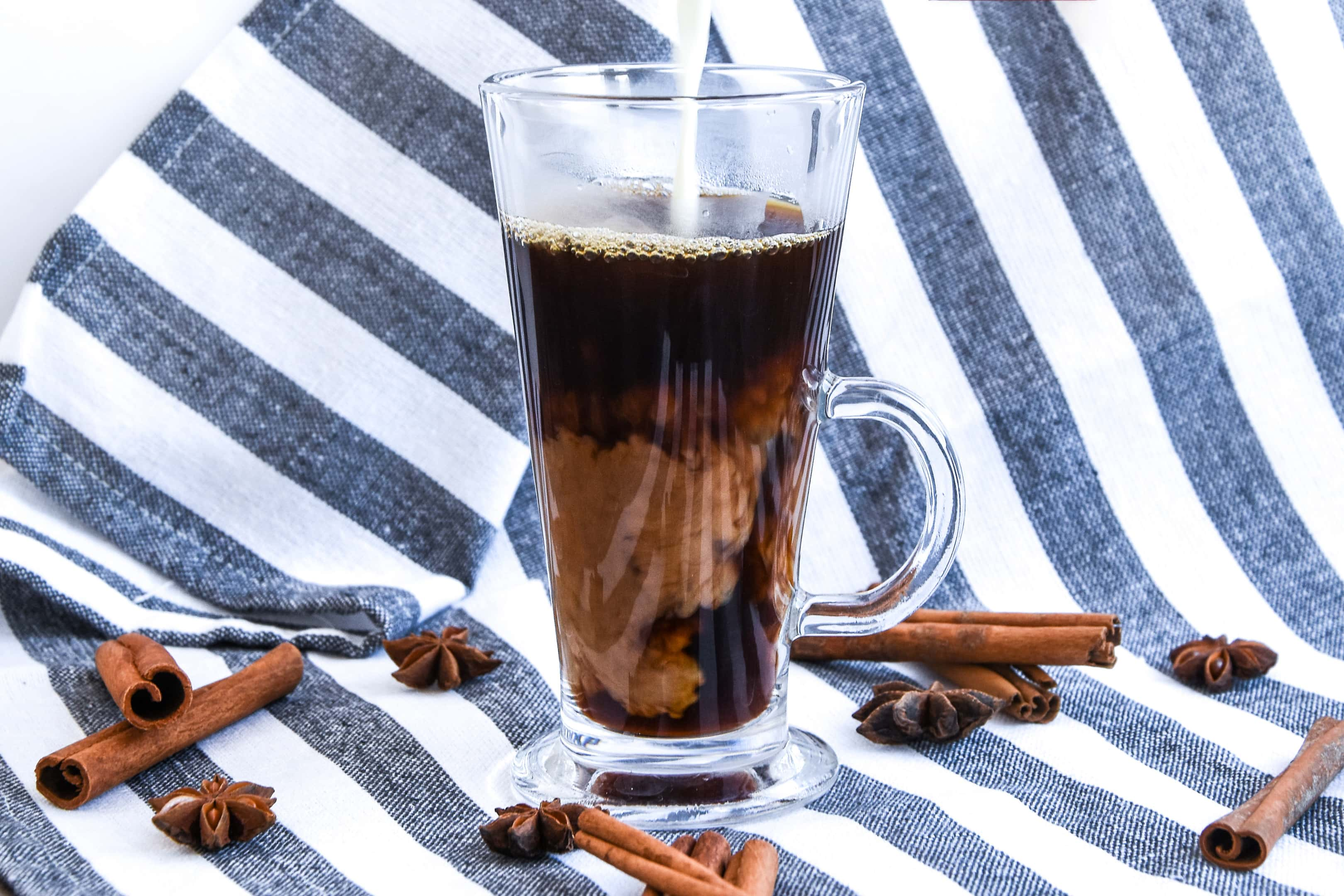 Pouring coffee creamer into glass with black coffee