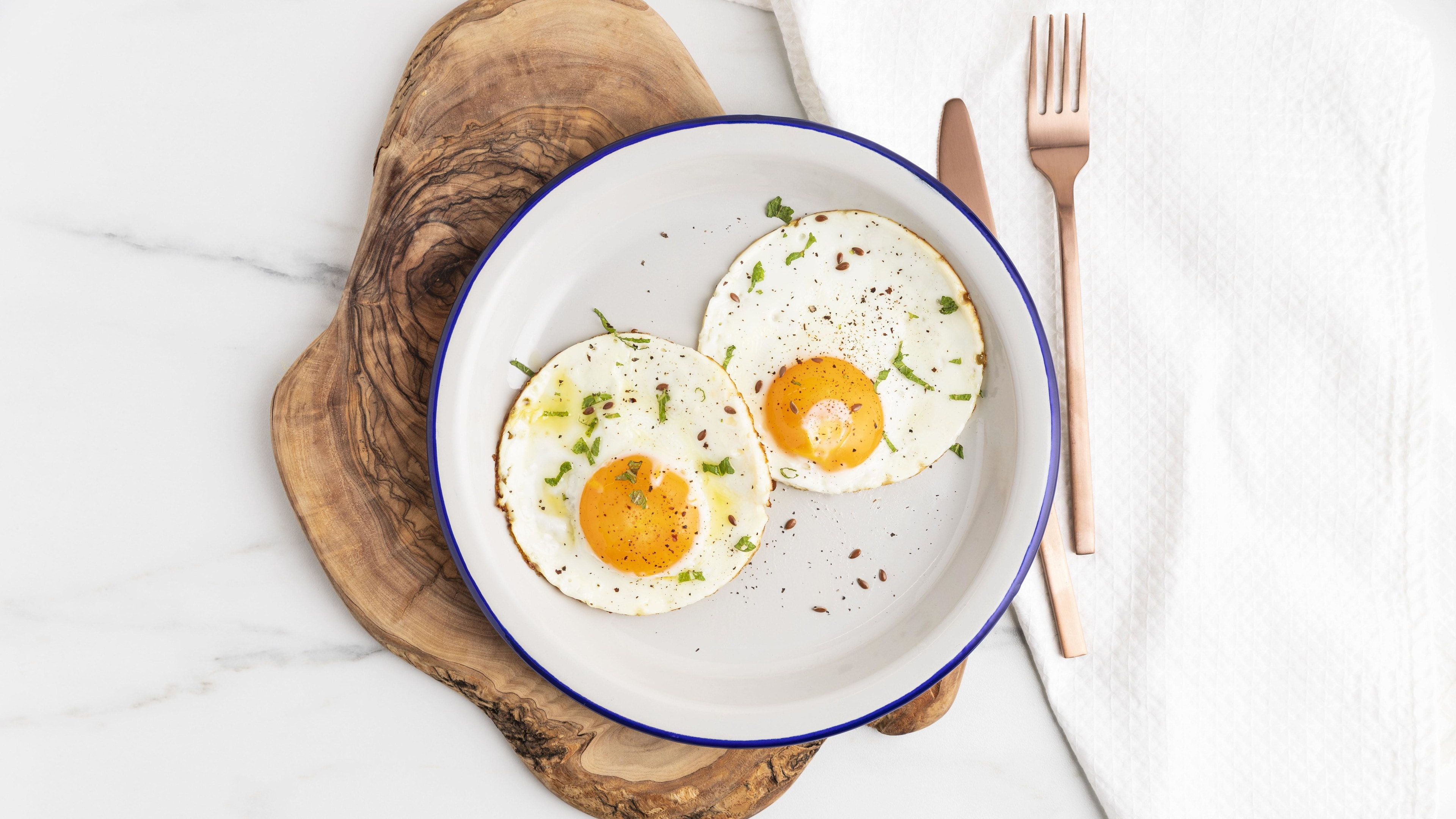 Fried eggs plate with cutlery on wooden board