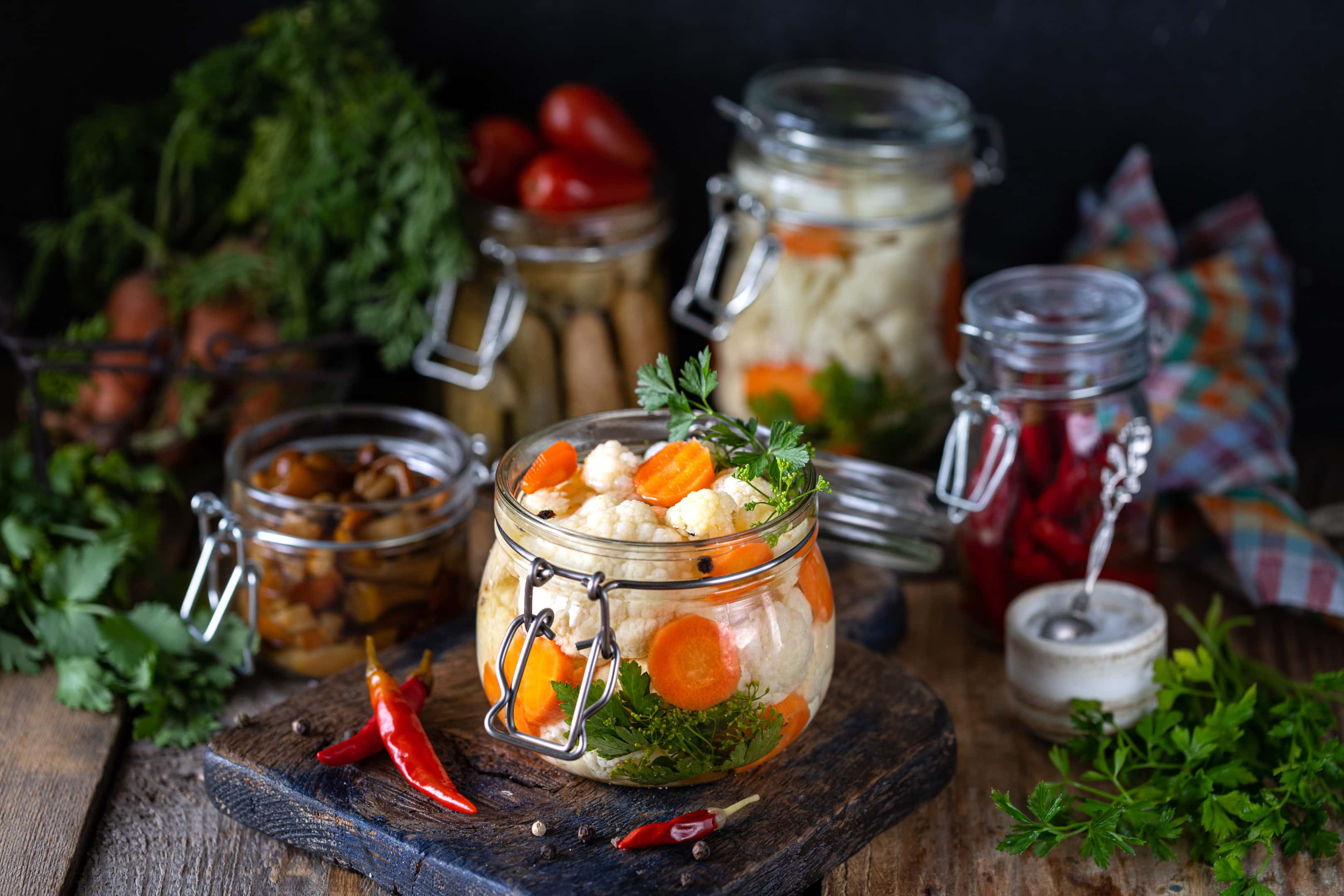 Fermented cauliflower with carrots in a glass jar on wooden table