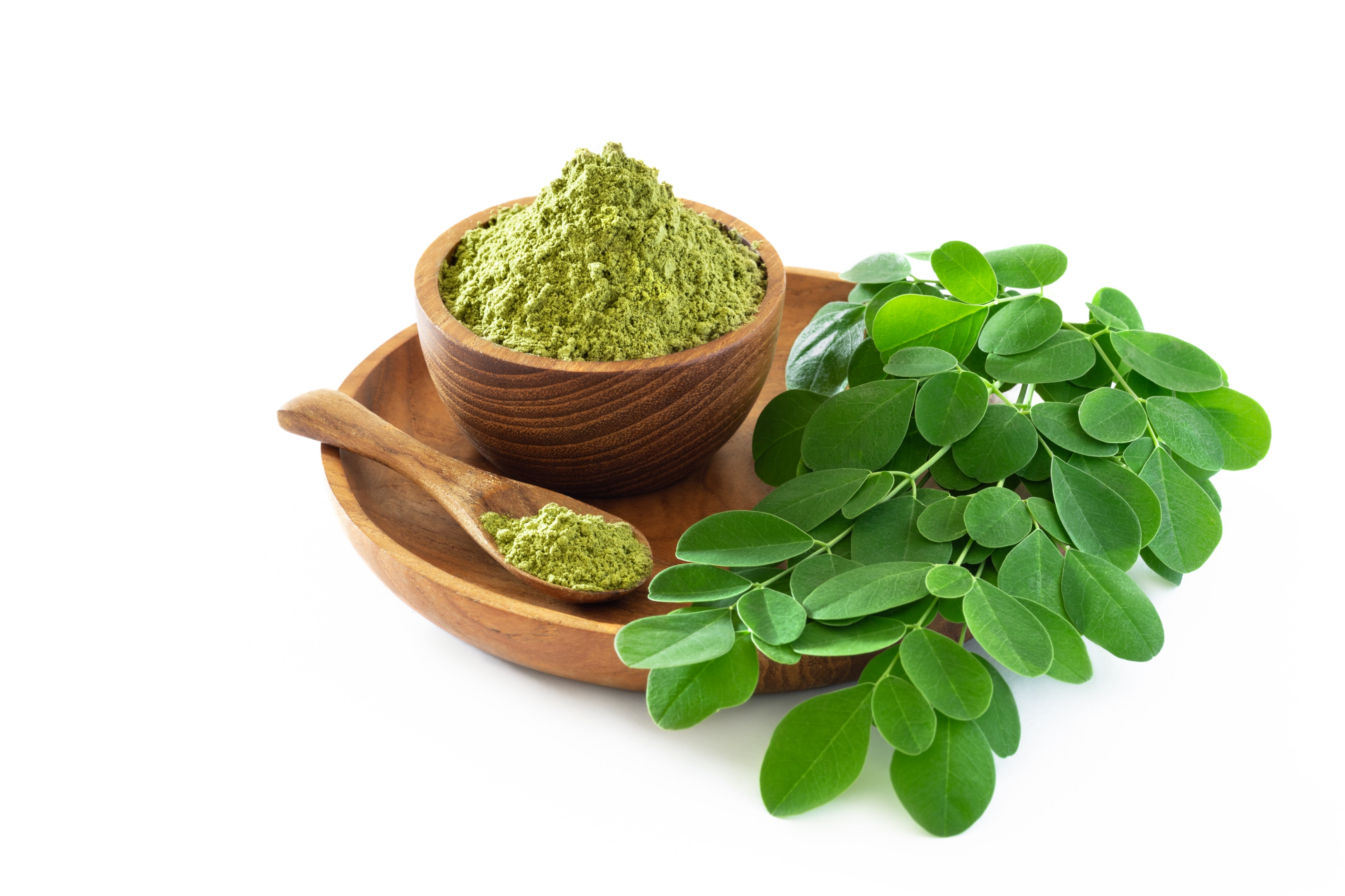 Moringa powder in wooden bowl with fresh moringa leaves