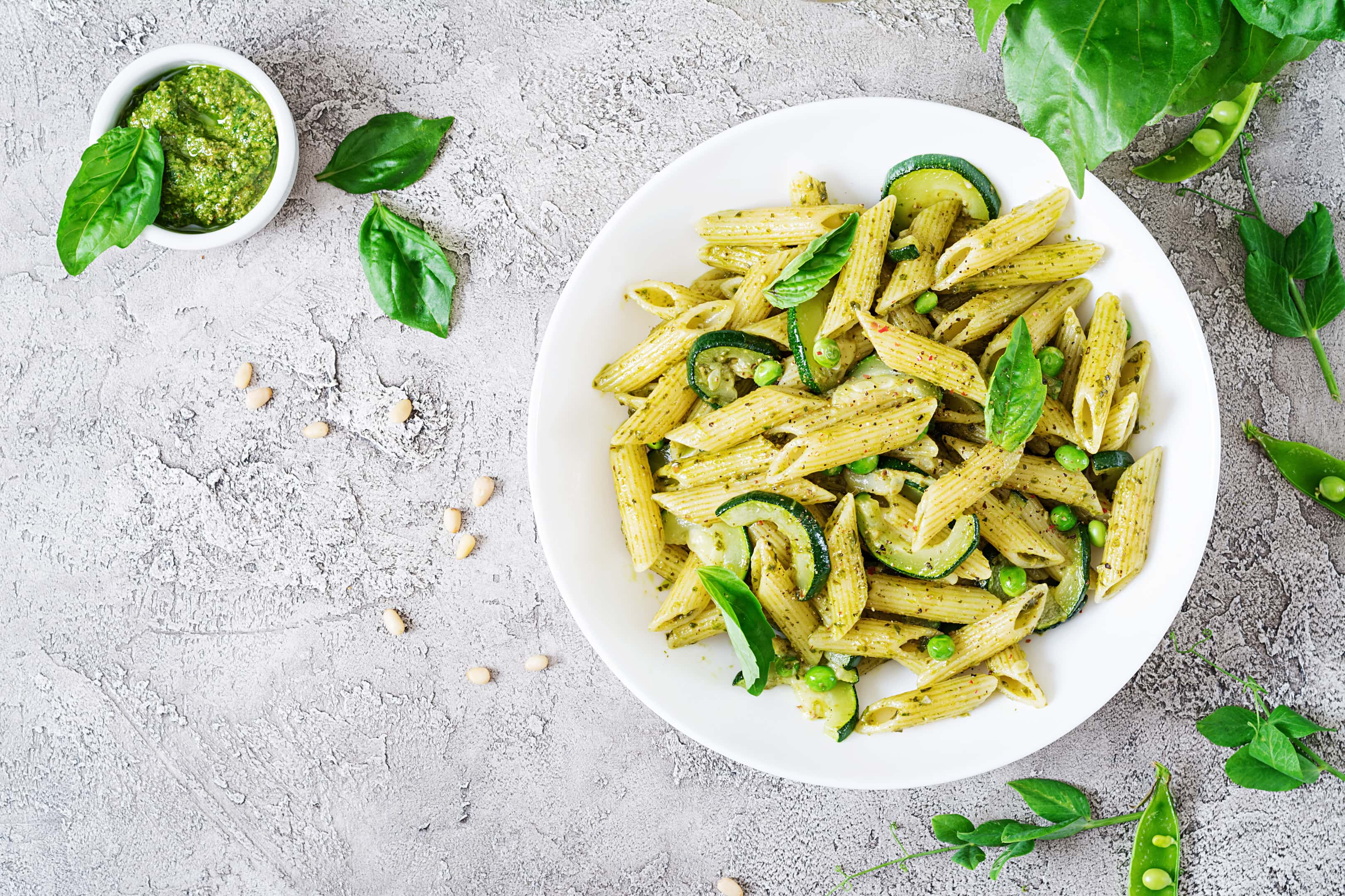 Penne pasta with pesto sauce, zucchini, green peas and basil